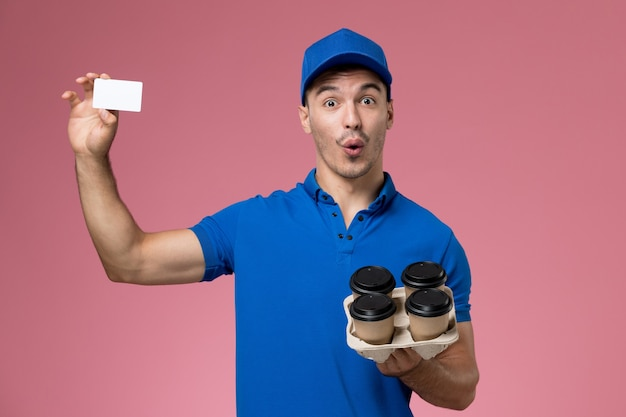Male courier in blue uniform holding delivery coffee cups and card on pink, uniform job worker service delivery