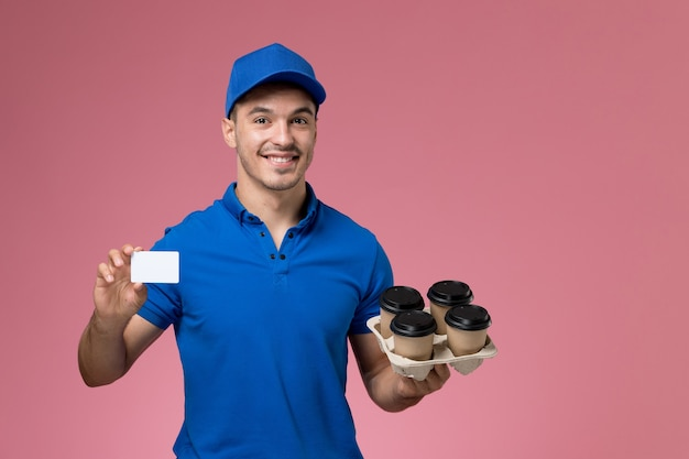 Male courier in blue uniform holding delivery coffee cups and card smiling on pink, uniform service job delivery