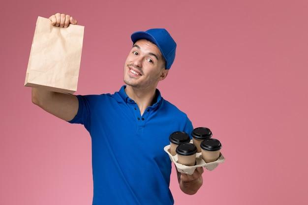 Corriere maschio in uniforme blu che tiene la consegna tazze da caffè pacchetto alimentare su rosa, consegna uniforme del servizio di lavoro