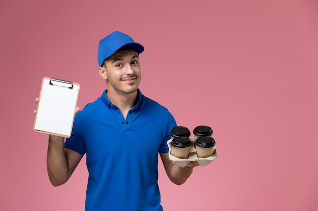 Corriere maschio in uniforme blu che tiene le tazze di caffè di consegna e il blocchetto per appunti sulla consegna rosa, uniforme del servizio del lavoratore di lavoro