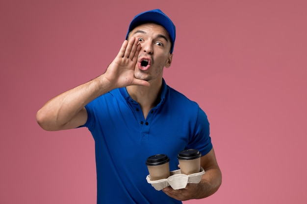 Male courier in blue uniform holding delivery coffee cups screaming on pink, uniform job worker service delivery