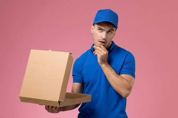 Male courier in blue uniform holding delivery food box opening it on pink, uniform service job delivery