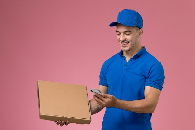 Male courier in blue uniform holding delivery food box and smartphone on pink, uniform job worker service delivery