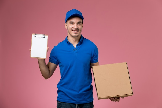 Male courier in blue uniform holding food box and notepad on pink, uniform service job delivery