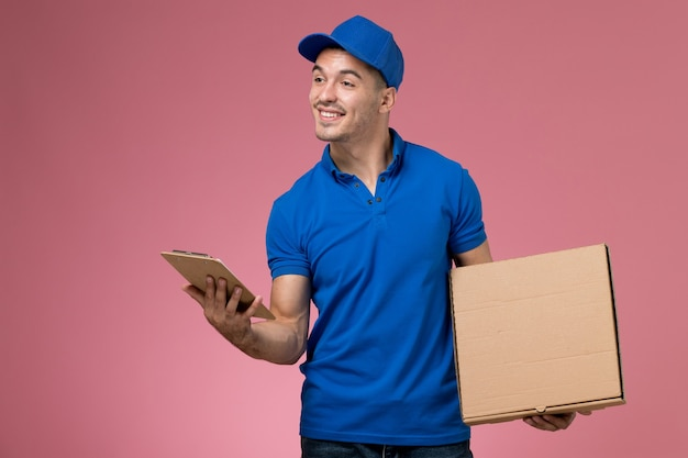 Male courier in blue uniform holding food box notepad with a smile on pink, worker uniform service delivery