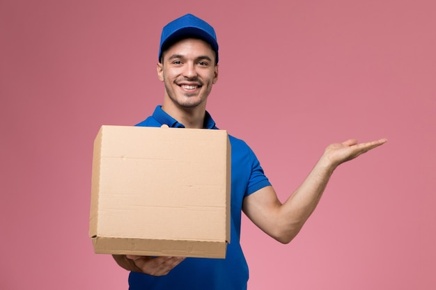 Male courier in blue uniform holding food box opening it and smiling on pink, uniform service job delivery