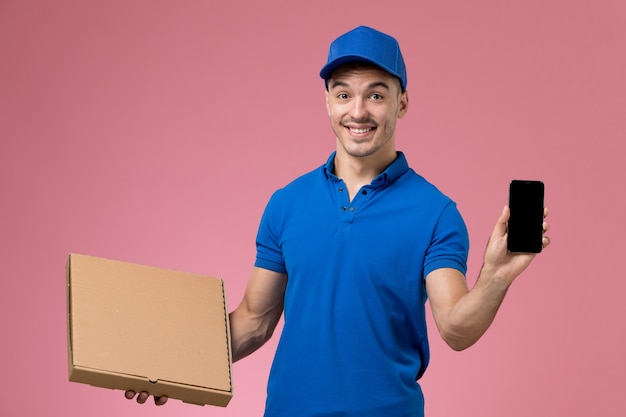 Male courier in blue uniform holding food box and phone smiling on pink, uniform job worker service delivery