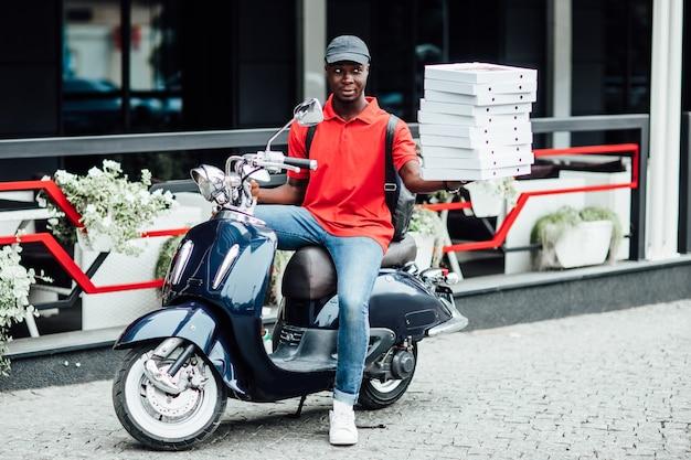 男性の宅配便業者は重い小包箱を運び、バイクはゆっくりと運転し、頭に保護用ヘルメットをかぶっています
