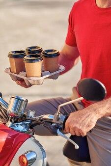 Мужской курьер, доставляющий кофе на скутере, выборочный фокус на четырех бумажных стаканчиках. концепция доставки еды