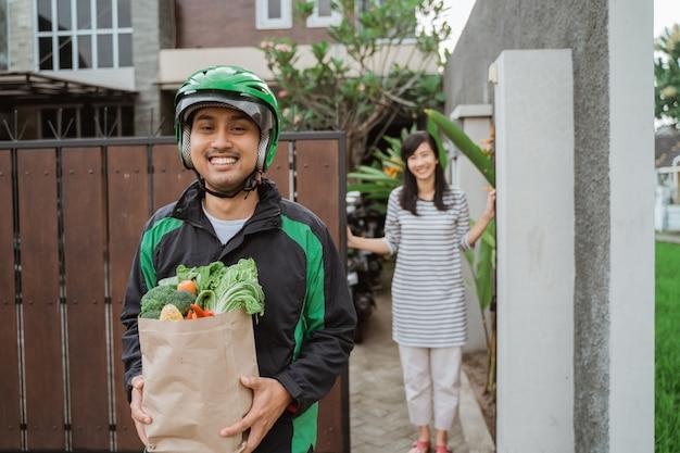 食料品を顧客に配達する男性の宅配便