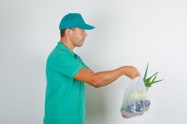 Курьер-мужчина доставляет полиэтиленовые пакеты с овощами в зеленой футболке с кепкой