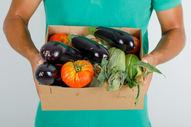 Male courier in green t-shirt holding vegetables in cardboard box