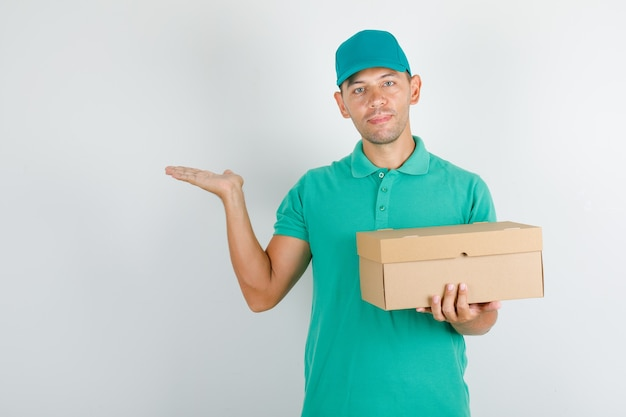 Male courier in green t-shirt with cap holding box and keeping opened hand