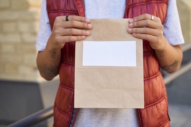 텍스트를 위한 복사 공간이 있는 작은 종이 가방을 들고 있는 남성 택배