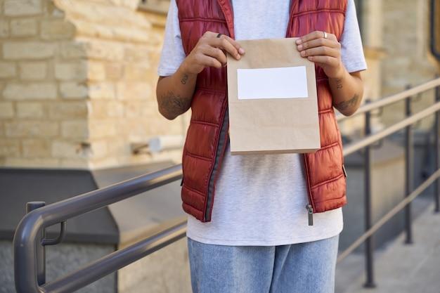 テキストwhのコピースペースと小さな紙袋を保持している男性の宅配便