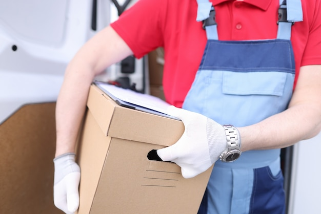 Курьер-мужчина держит картонную коробку с документами