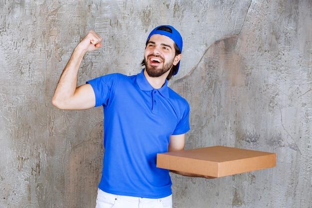 파란색 유니폼을 입은 남성 택배는 판지 테이크아웃 상자를 들고 긍정적인 손 기호를 보여줍니다.