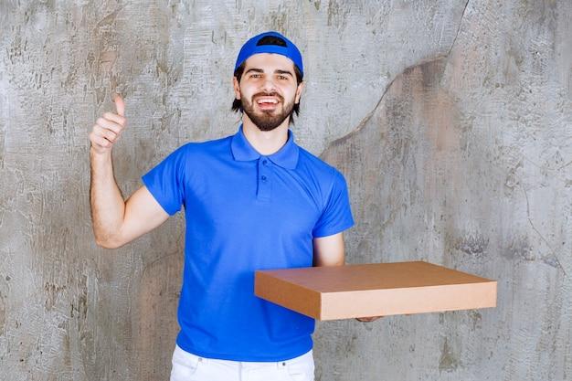 段ボールの持ち帰り用の箱を運び、肯定的な手のサインを示す青い制服を着た男性の宅配便。