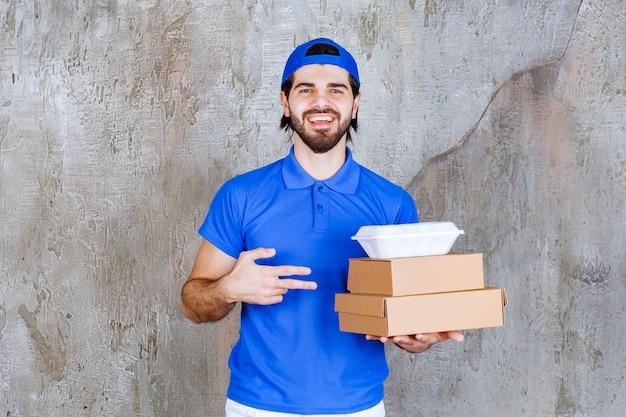 Курьер-мужчина в синей форме, несущий картонные и пластиковые коробки