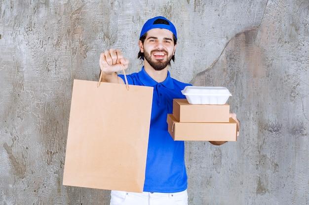 段ボールの小包、買い物袋、プラスチックの持ち帰り用の箱を運ぶ青い制服を着た男性の宅配便