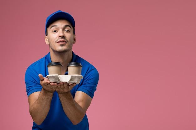 Курьер-мужчина в синей форме доставляет кофейные чашки на розовом, работник службы доставки униформы