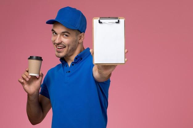 Курьер-мужчина в синей форме держит блокнот с коричневой кофейной чашкой на розовом, униформе по доставке работы