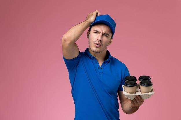 ピンク、労働者の制服サービスの提供を考えて茶色のコーヒーカップを保持している青い制服を着た男性の宅配便