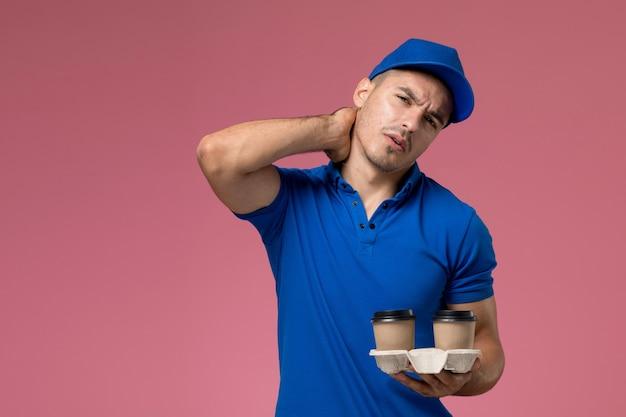 Курьер-мужчина в синей форме держит чашки для кофе с болью в шее на розовом, служба доставки униформы