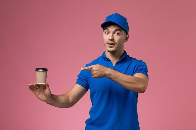 Курьер-мужчина в синей форме держит чашку кофе на розовом, униформа службы доставки