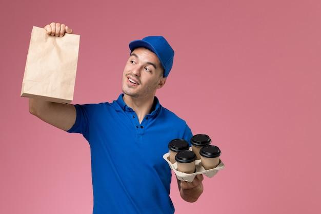 Курьер-мужчина в синей форме держит кофейные чашки и пакеты с едой на розовом, единообразная служба доставки