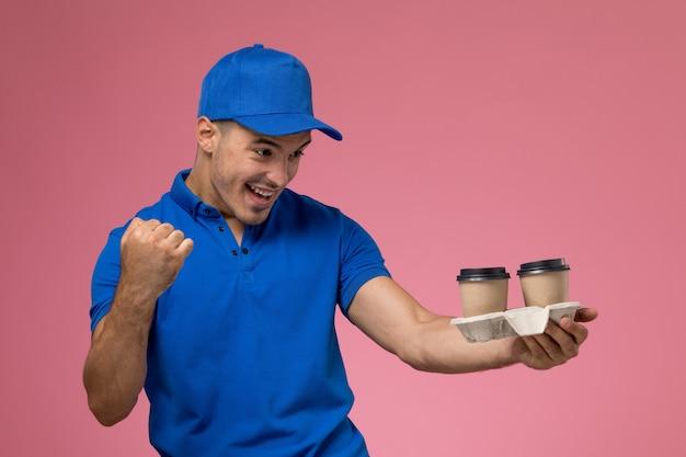 Курьер-мужчина в синей форме с кофейными чашками, аплодирующими розовым, униформа службы доставки работы