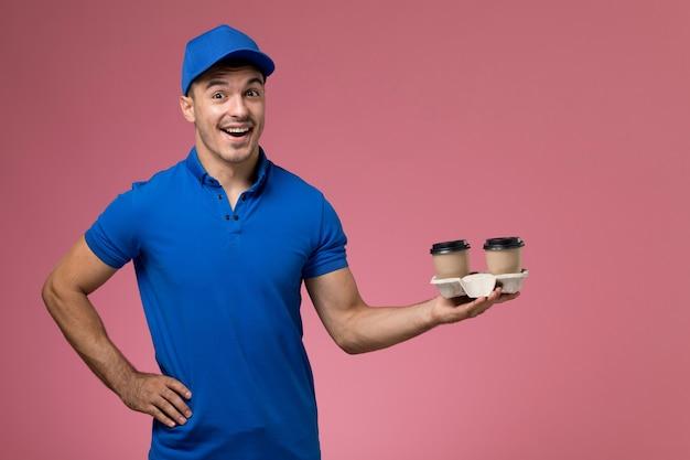 Курьер-мужчина в синей форме с кофейными чашками на розовом, работник службы доставки в униформе