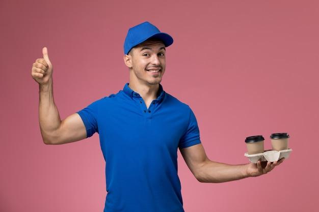 ピンクに笑みを浮かべてポーズをとるコーヒーカップを保持している青い制服の男性宅配便、労働者の制服サービスの提供