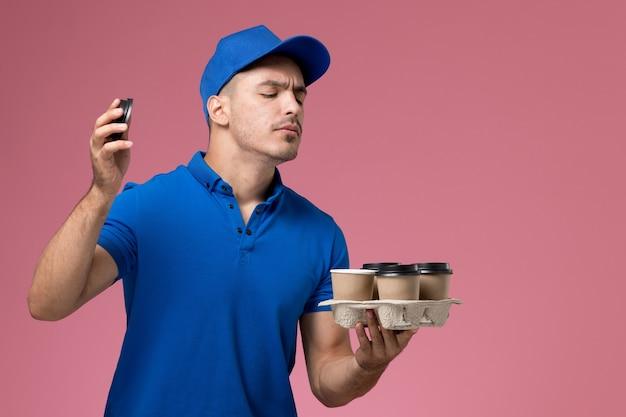 Курьер в синей форме с чашками кофе, нюхающий их на розовом, работник службы доставки в униформе