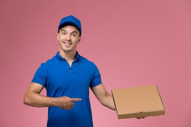 ピンクに微笑んでいる食品の配達ボックスを保持している青い制服を着た男性の宅配便、労働者の制服サービスの配達