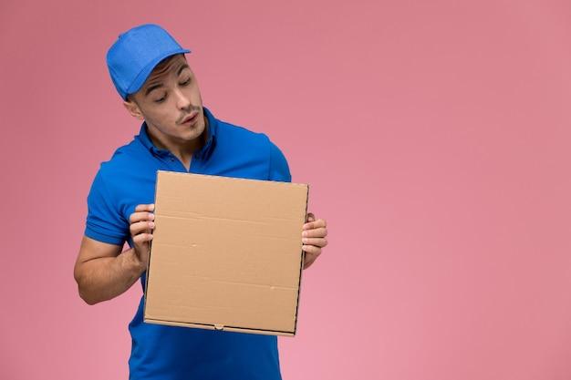 Мужской курьер в синей форме, держащий коробку доставки еды на розовом, служба доставки униформы рабочего