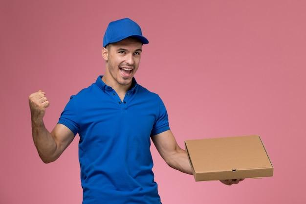 Курьер-мужчина в синей форме держит коробку доставки еды, радуется на розовом, доставка униформы рабочего рабочего