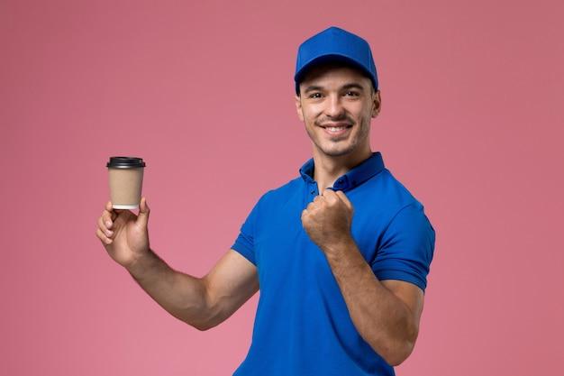 配達コーヒーカップを保持し、ピンクの制服の労働者サービスの配達を応援する青い制服の男性宅配便