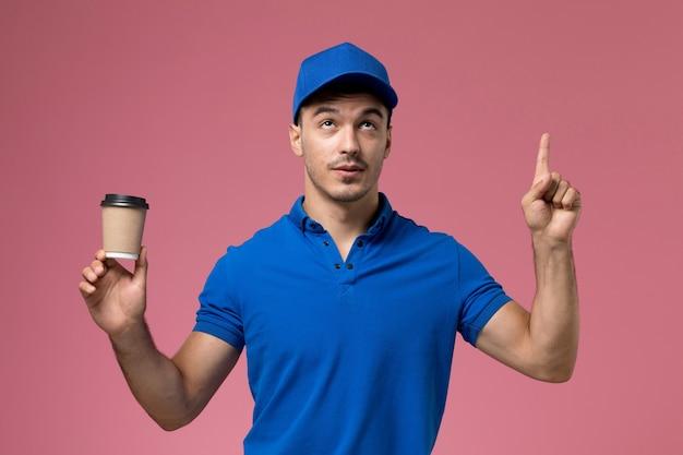 ピンクの均一なサービスの仕事の配達に配達コーヒーカップを保持している青い制服の男性の宅配便