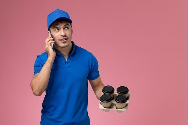 ピンクの制服の労働者サービスの配達で電話で話している青い制服を持った配達コーヒーカップの男性宅配便