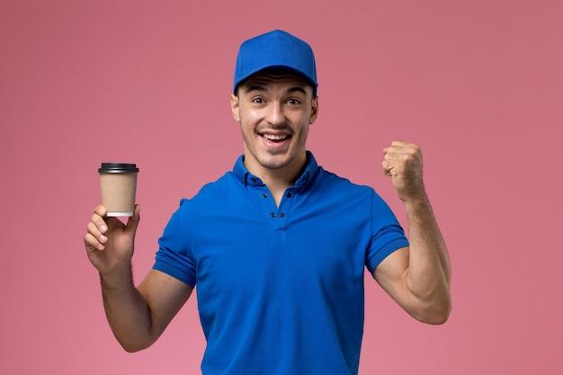 Мужчина-курьер в синей форме держит доставку кофе, улыбаясь в розовую, униформу службы доставки работы