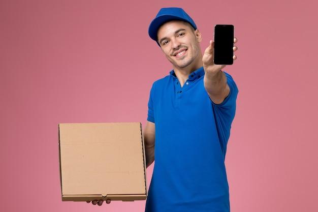 Мужчина-курьер в синей форме держит телефон с коробкой для еды на розовом, униформе работник службы доставки