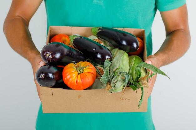 Курьер-мужчина в зеленой футболке держит овощи в картонной коробке