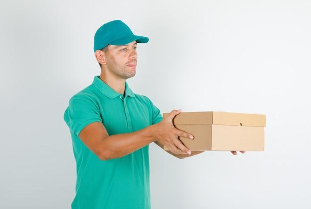 Курьер-мужчина в зеленой футболке с кепкой, доставляющей картонную коробку