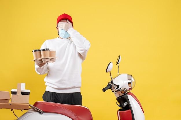 Мужской курьер в маске держит кофе на желтом