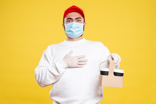 Мужской курьер в маске держит доставку кофе на светло-желтом
