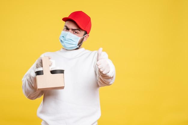 Мужской курьер в маске держит доставку кофе на желтом