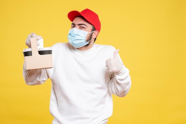 黄色の配達コーヒーを保持しているマスクの男性宅配便