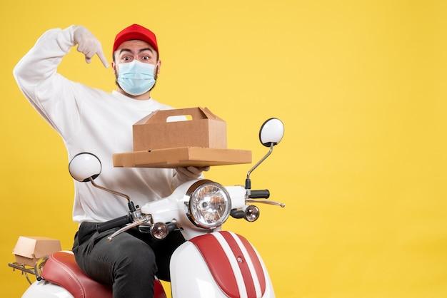 黄色の配達用食品を保持しているマスクの男性宅配便