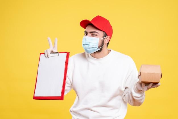 Курьер-мужчина в маске держит записку и небольшой пакет с едой на желтом